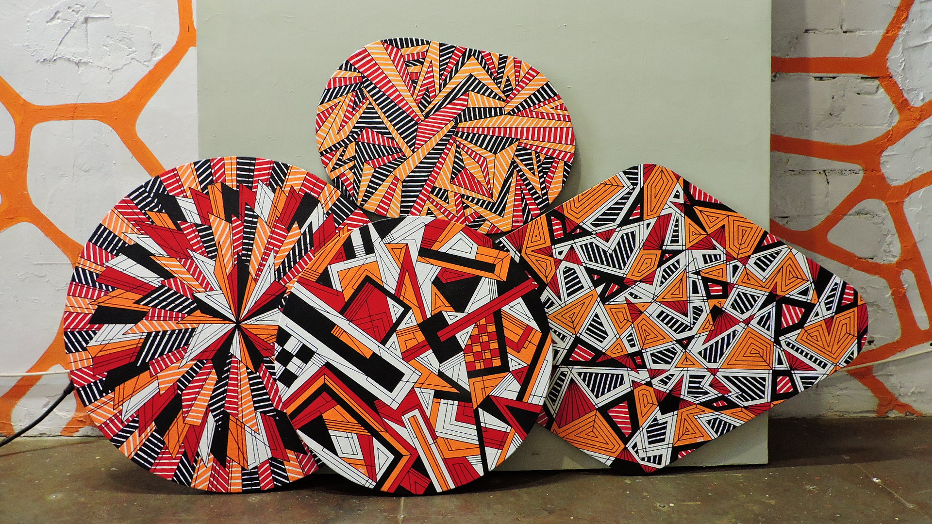 Four paintings of different geometric shapes, United by a common theme and color scheme